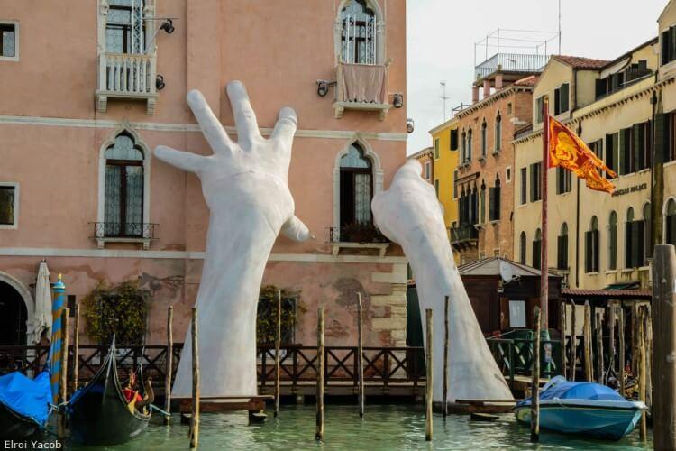בניין נתמך בפסל יד צילום שניתן לבצע מהים